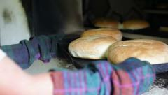 Taking baked bread from oven Stock Footage