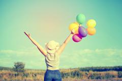 Vintage photo of young woman with colorful balloons in the field - stock photo