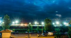 Car parking at night with street lights and dark clouds Stock Photos
