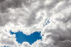 cumulus clouds on a blue sky background, bad weather - stock photo
