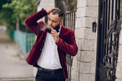 bearded man with e-cigarette - stock photo