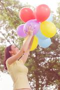 Freedom,Happy, Carefree, Relax, Young Woman with Colorful Balloons at beautif - stock photo