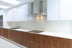 Actual modern kitchen in white and walnut wood - stock photo