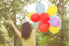 Happy Young Woman with Colorful Balloons at beautiful Summer Day Outdoor. Att Stock Photos