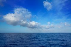 Stock Photo of cumulus clouds in blue sky over water horizon