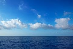 cumulus clouds in blue sky over water horizon - stock photo