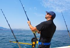 blue sea fisherman in trolling boat with downrigger - stock photo