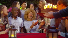 4K Happy group of friends at birthday party, woman blows out candles on her cake - stock footage