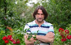 A man near the flowerbeds in the garden Stock Photos