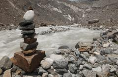Stacks of rocks near river flowing from melting Chalaadi glacier, Mestia, Georgi - stock photo
