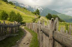 Road between the fence, Mestia, Georgia - stock photo