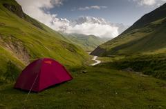 Red tent in caucasus valley with Mt. Shkhara in background Stock Photos