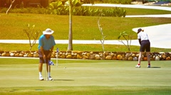 Golfers putting on a green at the Gulf Club, Datai Bay in Langkawi Malaysia Stock Footage