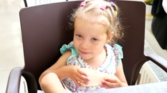Stock Video Footage of In confectionery - little girl eat sweet pastry cake with hands