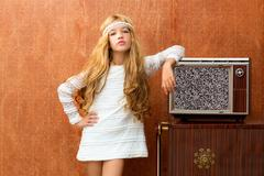 Blond vintage 70s kid girl with retro wood tv - stock photo