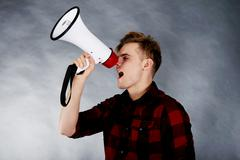Young man shouting in megaphone. - stock photo