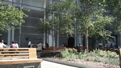 People sitting on a bench outside of a building Stock Footage
