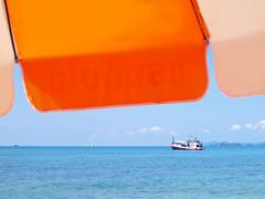 Sunshade with boat - stock photo