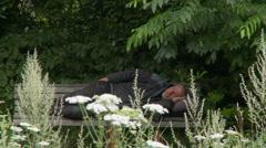 Sleeping homeless man in park Stock Footage
