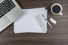 Laptop, paper pen Ruler and Eraser with cup of coffee - stock photo