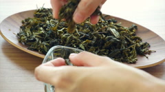 Hand setting dried green tea leaves Stock Footage
