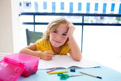 Child student kid girl bored with homework on desk Stock Photos