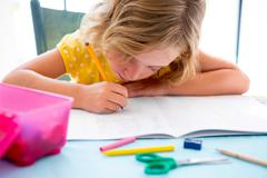 Child student kid girl writing with homework on desk - stock photo