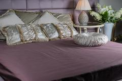 Purple bed wih beige pillows and classic round table Stock Photos