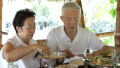 Asian senior elderly couple talking care of each other at meal  time Stock Footage