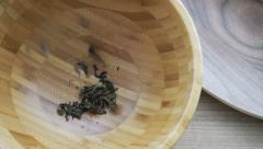Dried Tea leaf pouring in wooden bowl on wood background Stock Footage