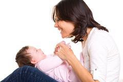 Baby girl on mother jeans knees playing together - stock photo