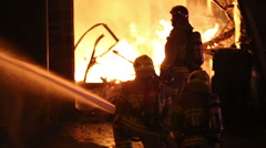 Spectacular house fire, firemen use hose in shadow Stock Footage