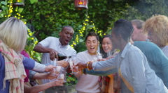 4K Happy group of friends at outdoor social gathering, one man pours champagne Stock Footage