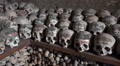 Skulls and bones in Charnel House at Hallstatt Austria HD Footage