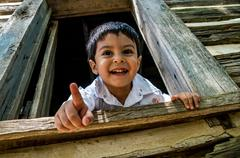 Latino child looking out a window - stock photo