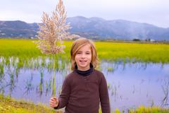 Blond kid girl outdoor holding spike in wetlands lake Stock Photos