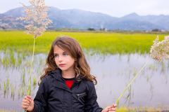 Brunette kid girl outdoor holding spike in wetlands lake Stock Photos