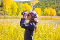 Explorer binocuar kid girl in yellow autumn nature - stock photo