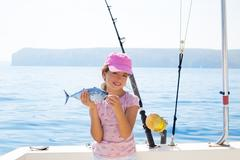 Child little girl fishing in boat holding little tunny fish catc Stock Photos