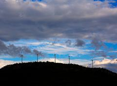 Sunset mountain with electric windmills Stock Photos