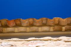 Clay roof tiles eaves detail on stone in blue sky - stock photo