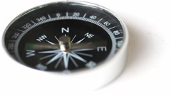 A compass lying on a white table and goes crazy Stock Footage