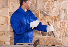 Stock Photo of Masonry mason stonecutter man with hammer working