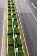 Empty Road with Green Fence and Traffic Sign - stock photo