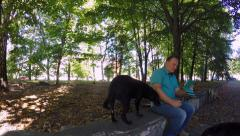 Male 40-50 years old in the park reading an e-book and petting stray dogs. Stock Footage