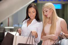 Pretty young women are going shopping together Stock Photos