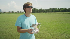 SLOW MOTION: Happy young pilot operating nd flying the drone Stock Footage
