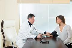 Doctor man checking blood pressure cuff on woman patient - stock photo