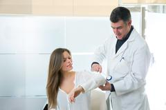 Doctor checking elbow with reflex round hammer to woman - stock photo