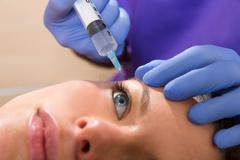 Anti aging facial mesotherapy syringe on woman face Stock Photos